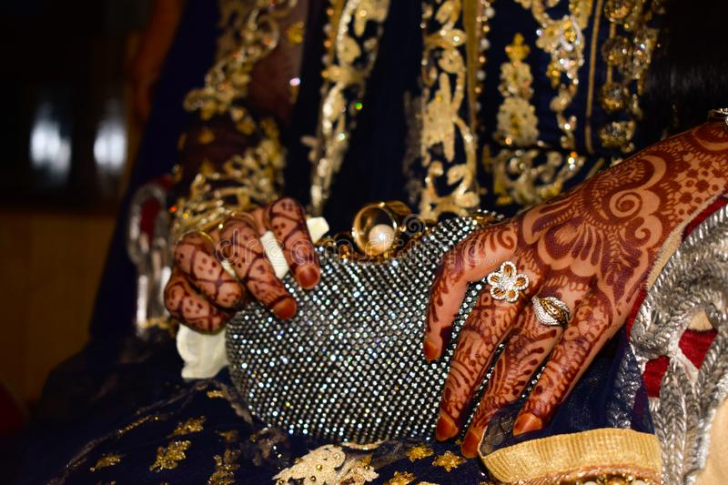 Indian bride with henna on hands. Gold rings on hand. Beautiful designs on hand. royalty free stock image