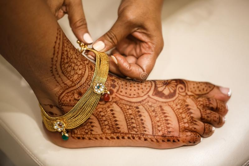 Indian bride putting foot bracelet on royalty free stock image