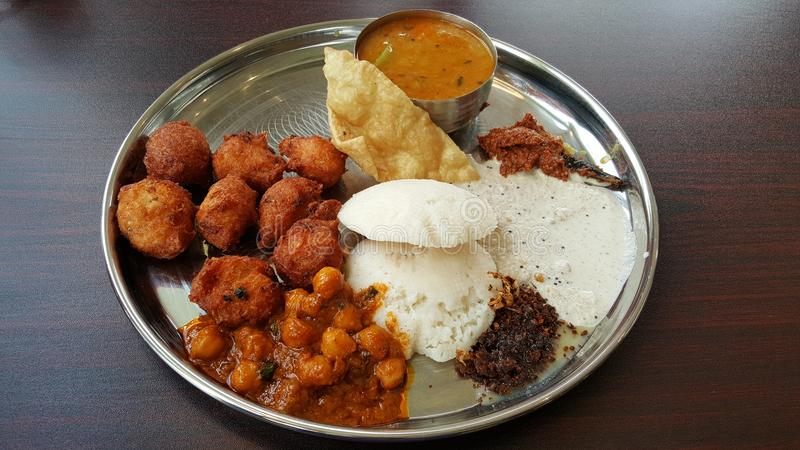 Indian buffet food. With Vada, Idly, Sambhar, Chutney, Ghobi manchurian and papad in a silver plate stock images
