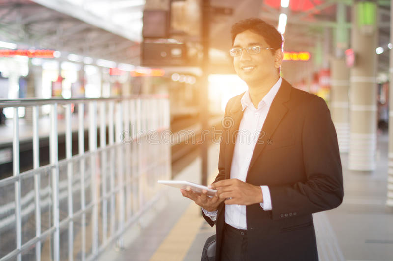 Indian business male using tablet computer. While waiting for train royalty free stock photo