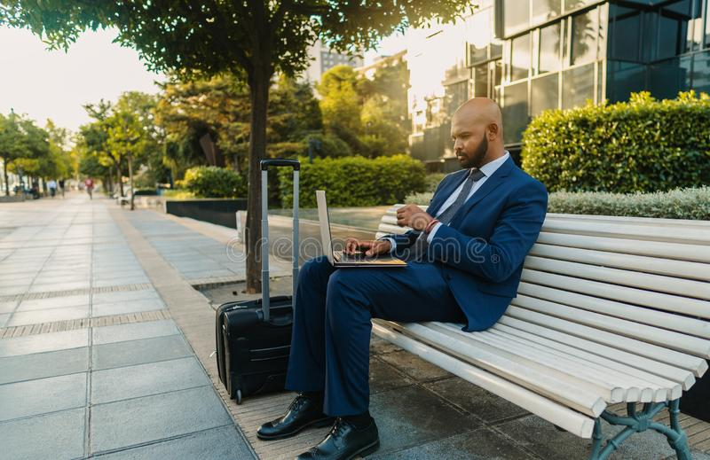 Indian businessman holding laptop notebook wearing blue suit near office stock photo