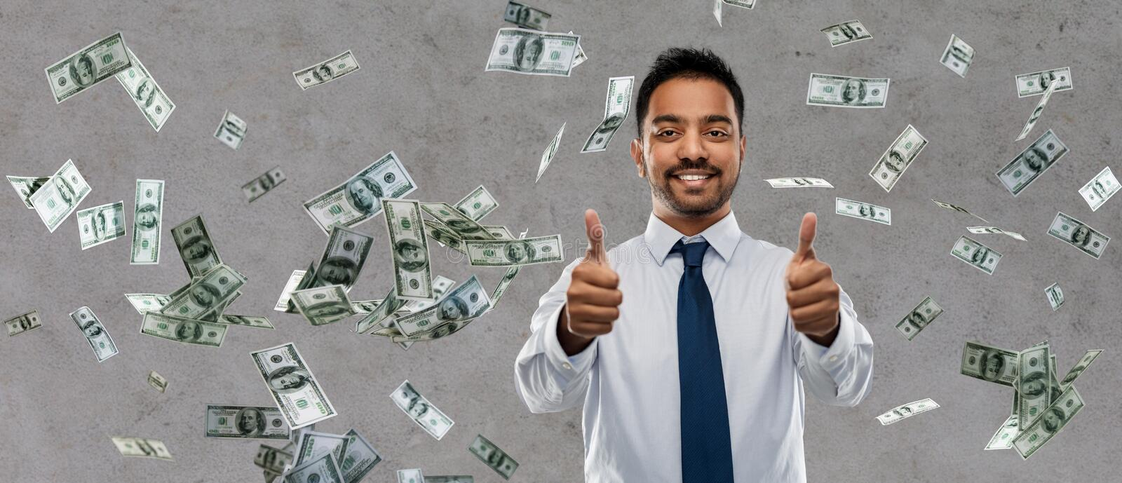 Indian businessman showing thumbs up over money. Business, office worker and people concept - smiling indian businessman showing thumbs up over money rain on stock photo