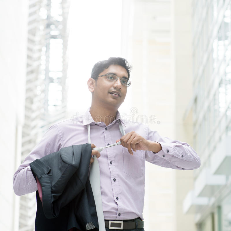 Indian businessman taking off his tie. Portrait of a Indian businessman taking off his tie after working hours, walking at modern building royalty free stock images