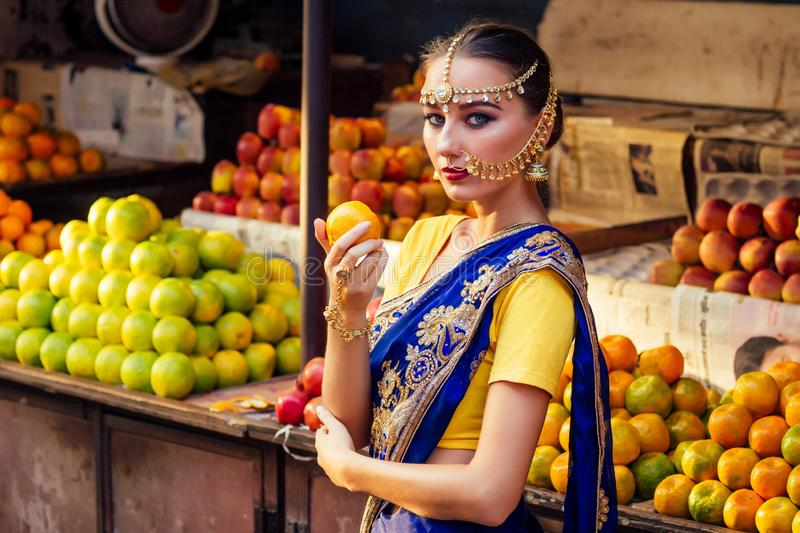 Indian Caucasian woman in traditional dress.hindu model golden kundan jewelry set bindi earrings and nose ring piercing royalty free stock photography