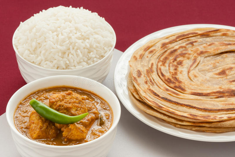 Indian chicken curry meal. Closeup view of Indian chicken curry meal with rice and wheat parotta (Indian bread). Green chilli used as garnish. Natural light used royalty free stock images