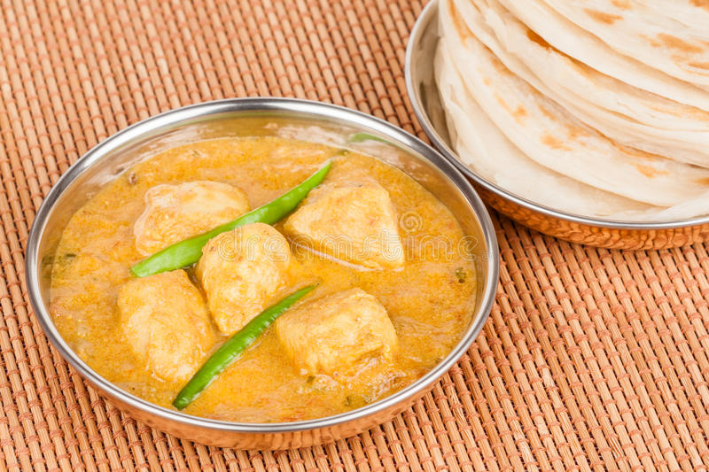 Indian Chicken Curry with Parotta. Indian chicken curry served with parotta (indian bread) in authentic copper utensils. Green chilli used as garnish royalty free stock images