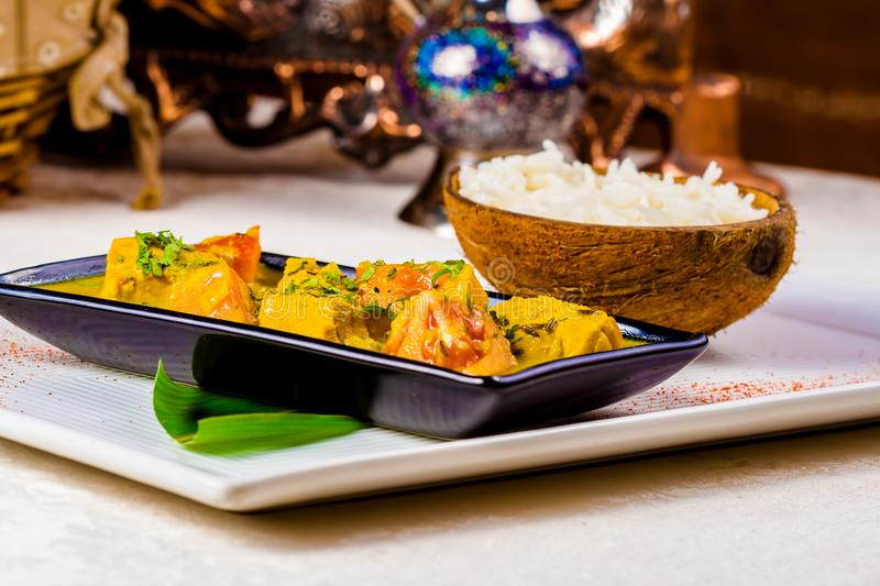 Indian chicken curry and rice. In coconut bowl stock photos