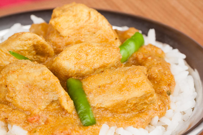 Indian Chicken Curry with Rice. Indian chicken curry served on rice in authentic copper utensil. Green chilli used as garnish. Shallow Depth of field royalty free stock photos