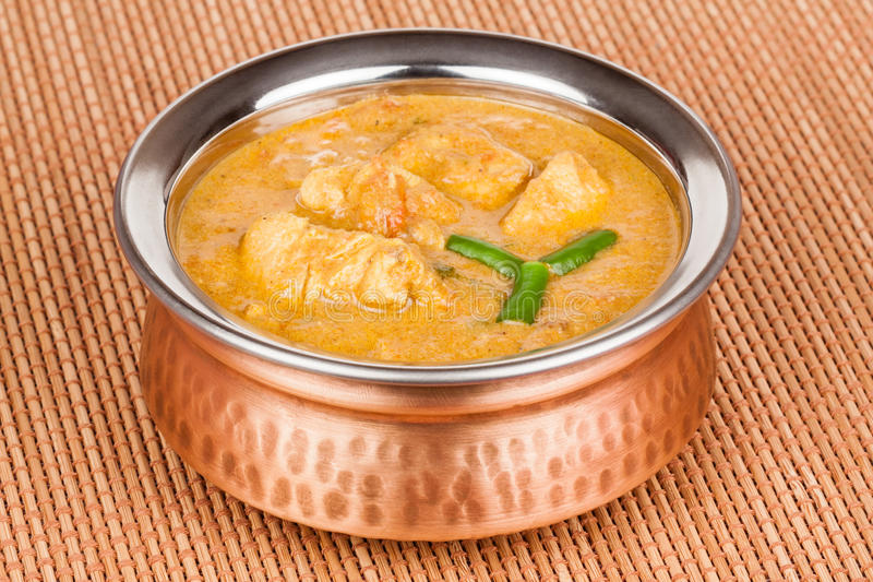 Indian Chicken Curry. Served in authentic copper bowl. Green chilli used as garnish stock photography
