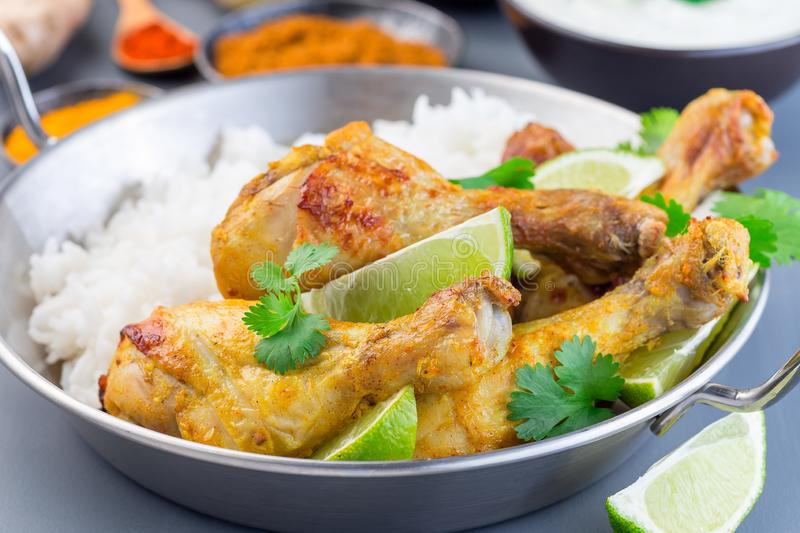 Indian chicken tandoori, marinated in greek yogurt  and spices, served with lime wedges, cilantro and basmati rice, horizontal. Indian chicken tandoori royalty free stock image