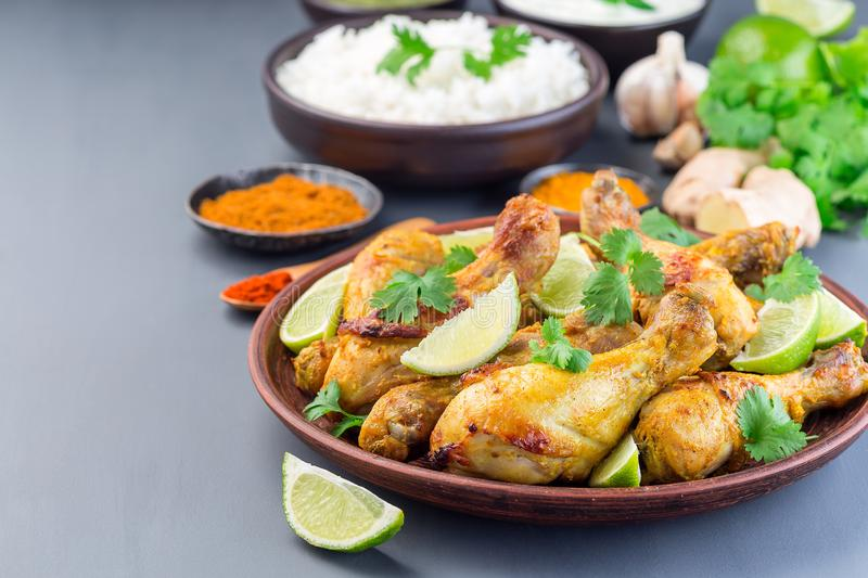 Indian chicken tandoori, marinated in greek yogurt  and spices, served with lime wedges and cilantro, horizontal,   copy space royalty free stock images