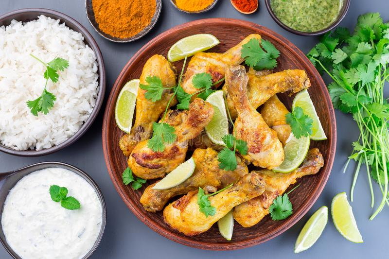 Indian chicken tandoori, marinated in greek yogurt  and spices, served with lime wedges and cilantro, horizontal,  top view stock images