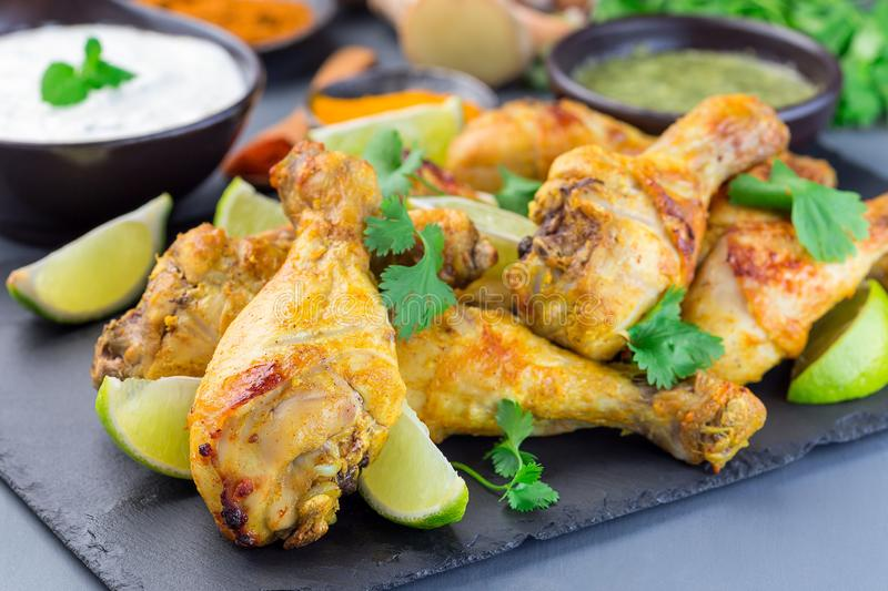 Indian chicken tandoori, marinated in greek yogurt  and spices, served with lime wedges and cilantro on a slate plate, horizontal. Indian chicken tandoori stock image