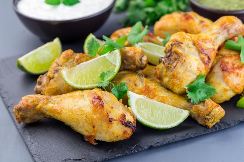 Indian chicken tandoori, marinated in greek yogurt  and spices, served with lime wedges and cilantro on  slate plate, horizontal. Indian chicken tandoori royalty free stock photography