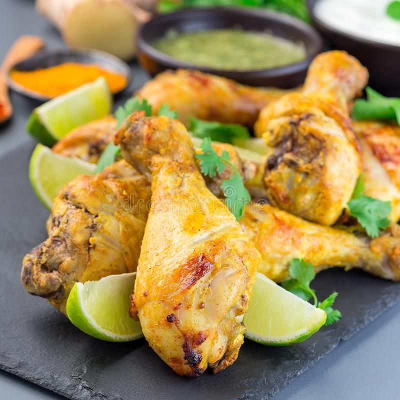 Indian chicken tandoori, marinated in greek yogurt  and spices, served with lime wedges and cilantro on a slate plate, square. Format food dinner drumstick meat stock photo