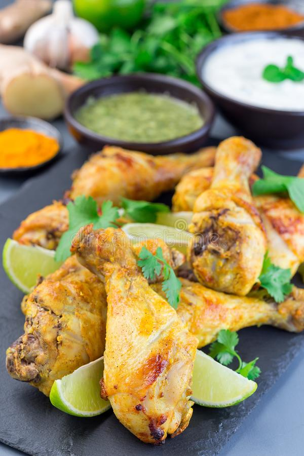 Indian chicken tandoori, marinated in greek yogurt  and spices, served with lime wedges and cilantro on slate plate, vertical. Indian chicken tandoori, marinated royalty free stock image
