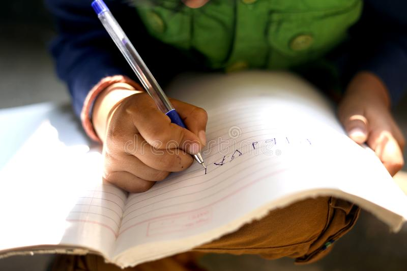 Indian child writing on note book. Writing hand stock photos