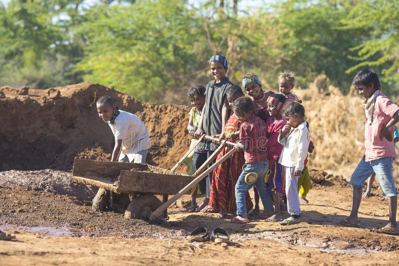 Indian Childhood. Andoure, India - December 21, 2017: indian children collecting mud for preparing brick, children love to help there parents, daily wage worker stock photography