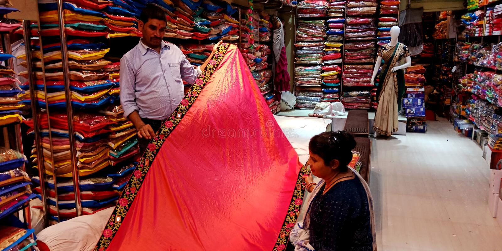 indian clothes seller showing designers sari to lady customer at showroom stock photo