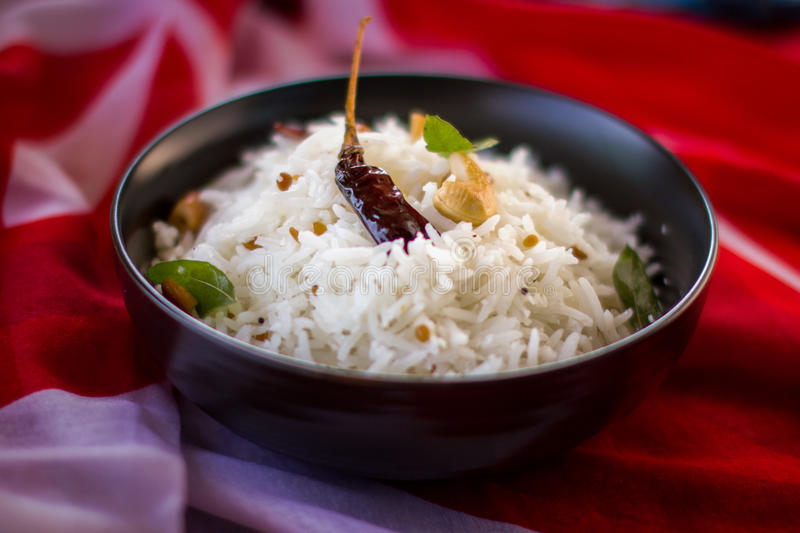 Indian Coconut Rice. Garnished with curry leaves, cashew nuts and dried chilli stock photography