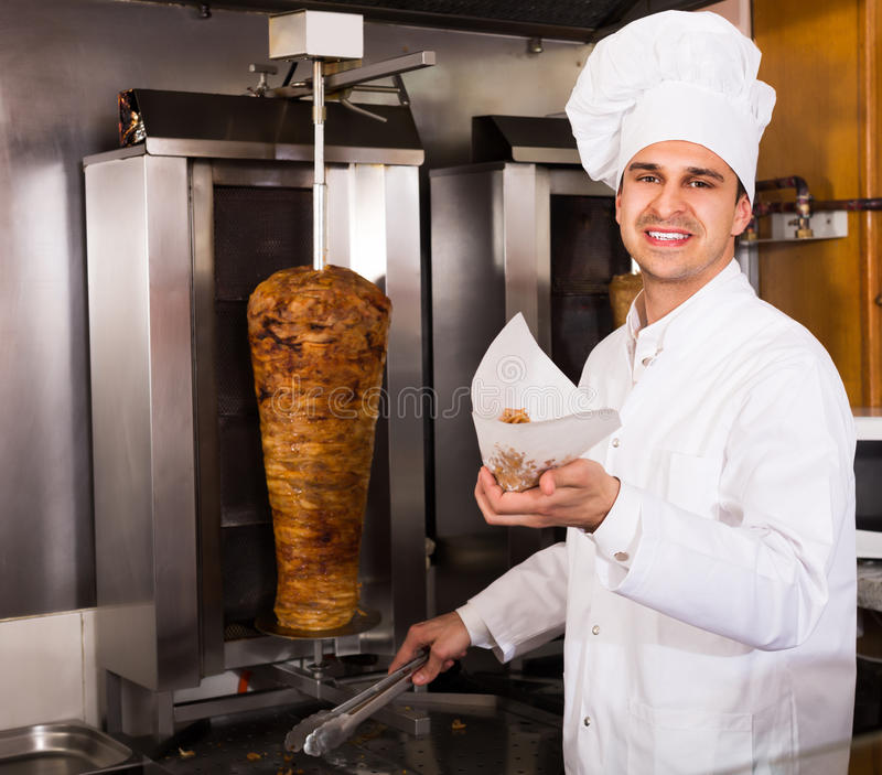 Indian cook offering kebab at counter. And smiling stock image