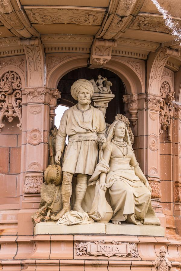 Indian couple at base of Doulton Fountain, Glasgow Scotland UK. Glasgow, Scotland, UK - June 17, 2012: Doulton Fountain on Glasgow Green. Brown stone statues of stock photography