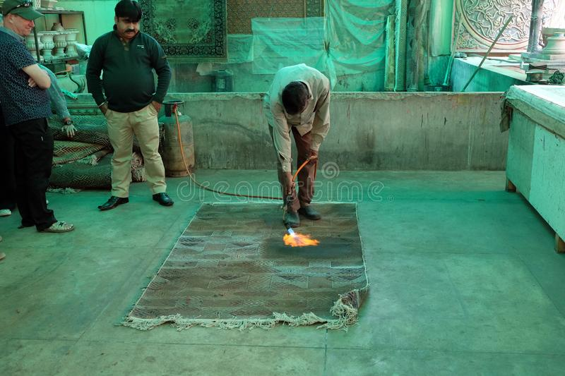 Indian craftsman using a blow torch to singe the back of a hand knotted rug. In Jaipur, Rajasthan, India on February 16, 2016 royalty free stock image