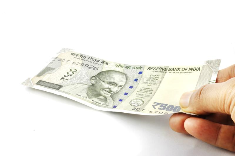 Indian Rupees in hand. Indian currency, five hundred rupees note held in hand. Giving Money royalty free stock images