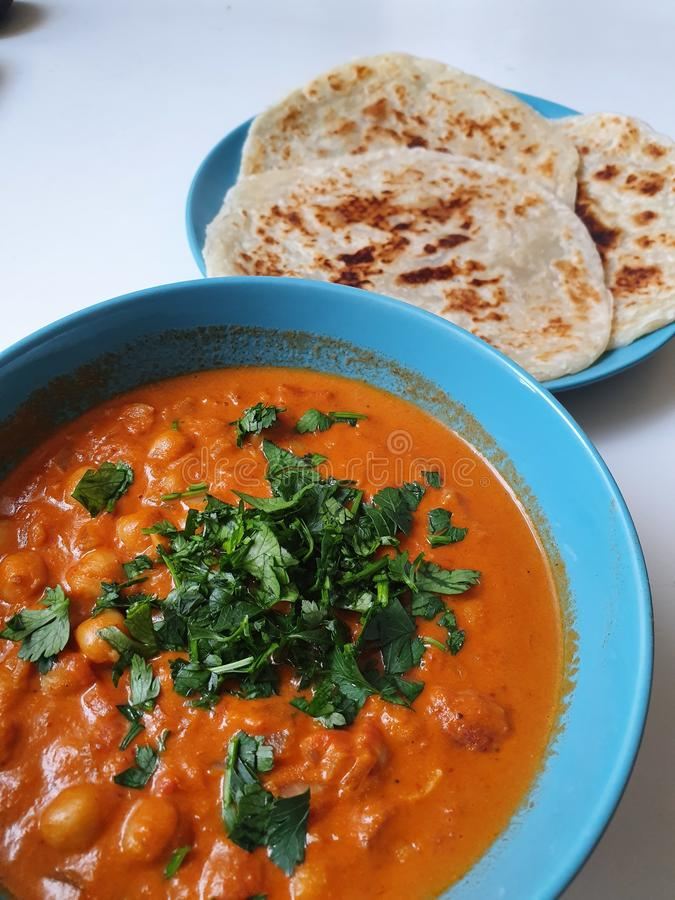 Indian Curry in a bowl with bread or roti. stock image