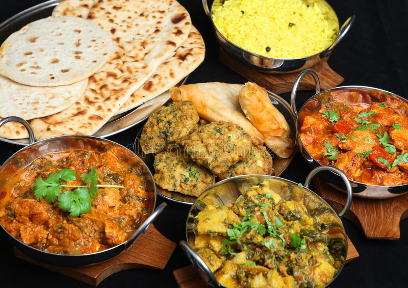 Indian Curry Food Selection. Indian food with curries, rice, naan bread, samosas and pakora royalty free stock image