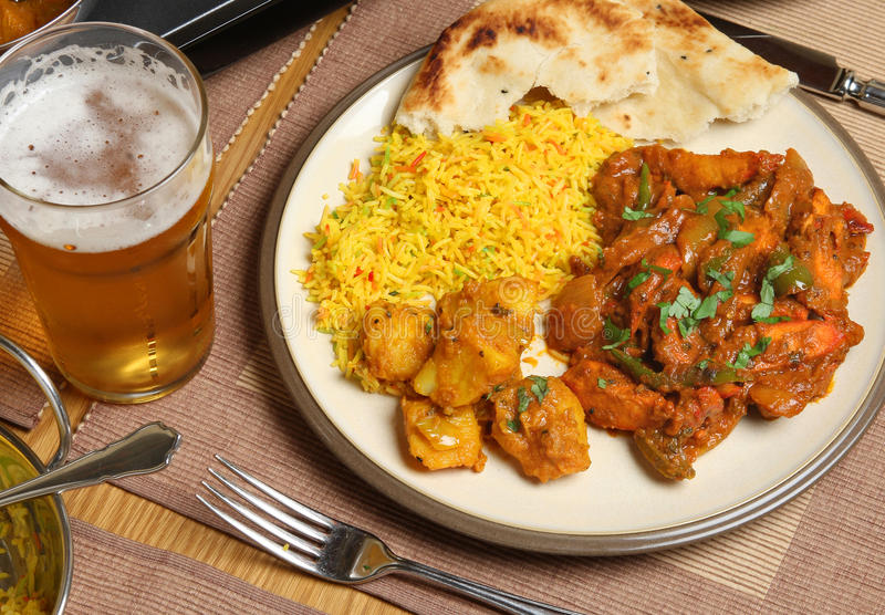 Indian Curry Meal. Indian chicken jalfrezi curry meal with Bombay aloo and pilau rice royalty free stock images