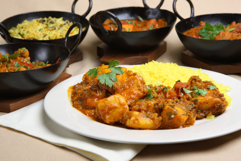Indian Curry Meal. Chicken pathia curry with rice and Bombay aloo royalty free stock image