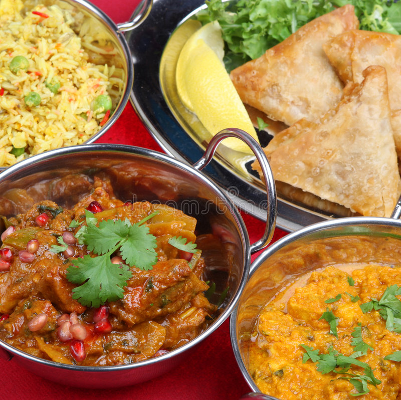 Indian Curry Meal Food. Lamb jalfrezi with rice, vegetables and samosas stock photography