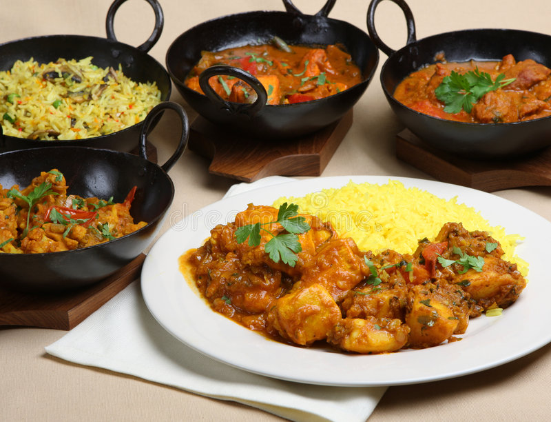 Indian Curry Meal Food. Chicken pathia with Bombay aloo and pilau rice with other curries in steel korai dishes royalty free stock photography