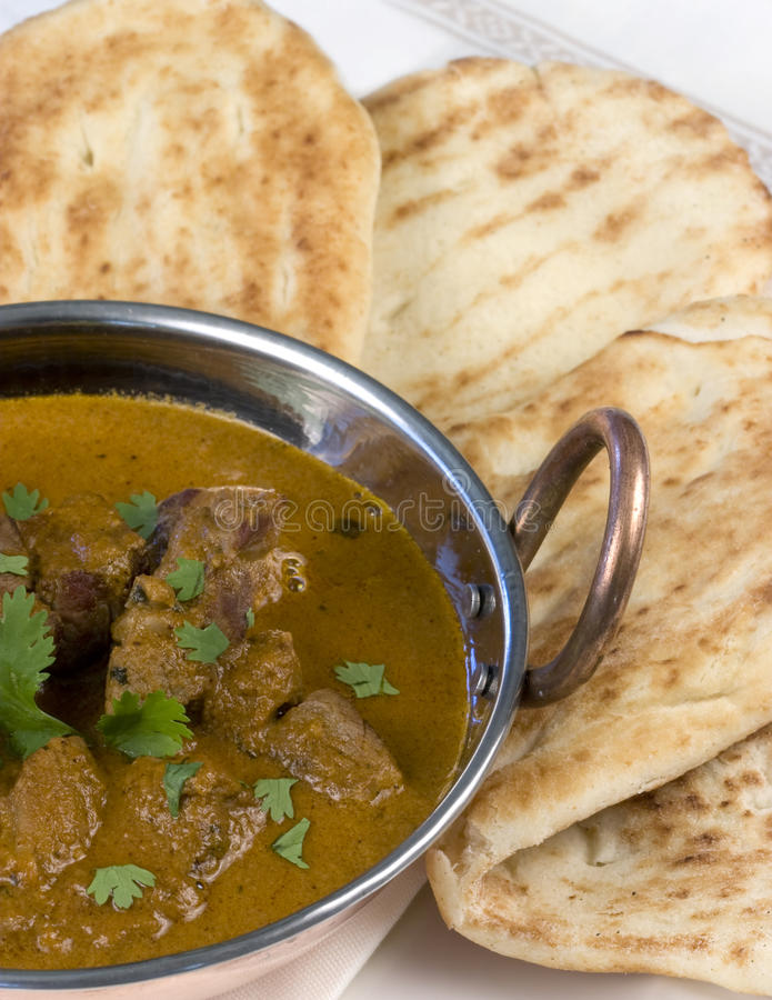 Indian Curry with Naan Bread - vertical. A lamb curry garnished with fresh coriander and served in a copper bowl with fresh naan bread served on side stock photo