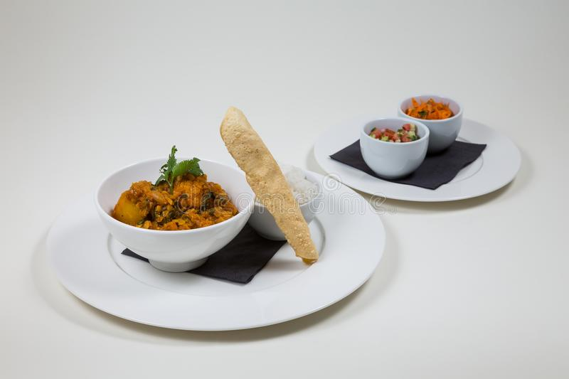 Indian Curry in a white bowl with rice on a white plate on a white background isolated stock photo