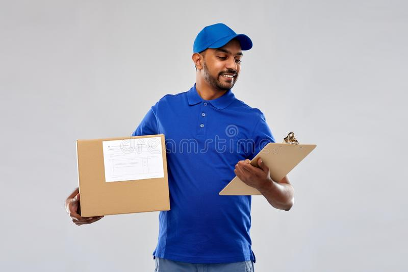 Indian delivery man with parcel box and clipboard. Mail service and shipment concept - happy indian delivery man with parcel box and clipboard in blue uniform stock images