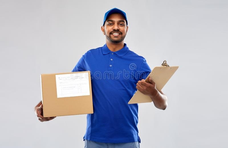 Indian delivery man with parcel box and clipboard. Mail service and shipment concept - happy indian delivery man with parcel box and clipboard in blue uniform stock image