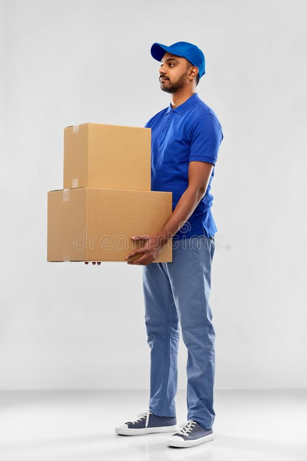 Indian delivery man with parcel boxes in blue. Mail service and shipment concept - indian delivery man with parcel boxes in blue uniform over grey background royalty free stock photos