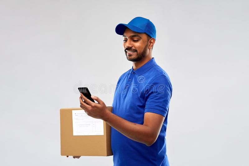 Indian delivery man with smartphone and parcel box. Mail service, technology and shipment concept - happy indian delivery man with smartphone and parcel box in stock images