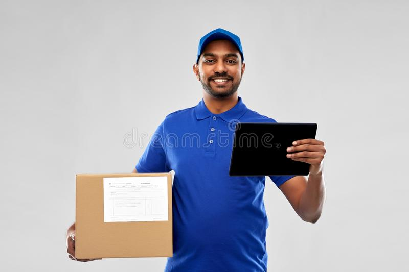 Indian delivery man with tablet pc and parcel box. Mail service, technology and shipment concept - happy indian delivery man with parcel box and tablet computer stock photo