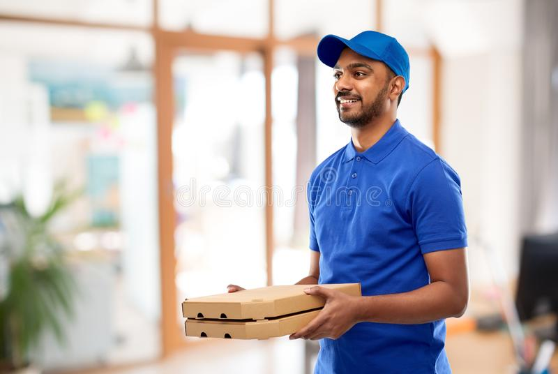 Indian delivery man with takeaway pizza at office. Takeaway service and people concept - happy indian delivery man with pizza boxes in blue uniform over office royalty free stock photography