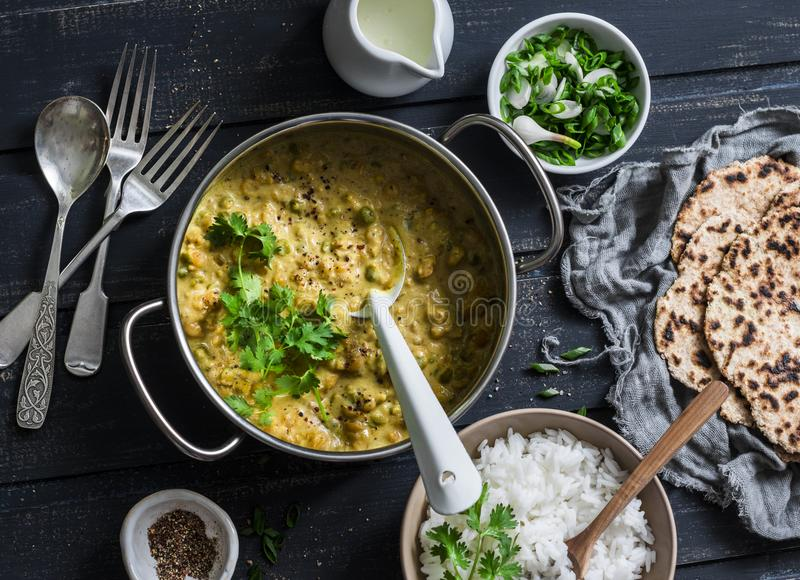 Indian dhal in cooking pan with jasmine rice, coriander and whole grain flatbread on dark background, top view. Flat lay royalty free stock photo