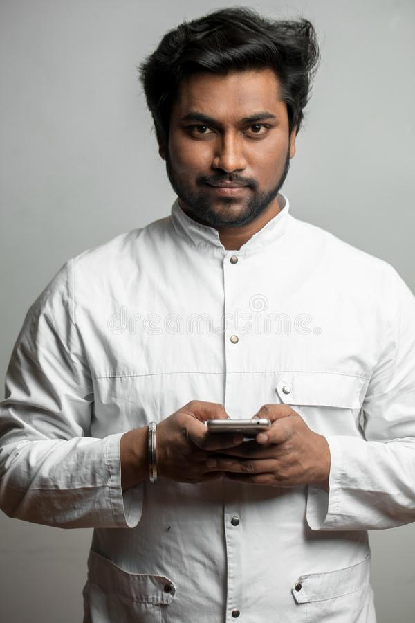 Indian doctor with smart phone. Indian doctor using smart phone. prescribe medicine with phone stock photography