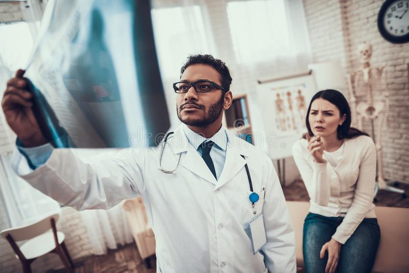 Indian doctor seeing patients in office. Doctor is looking at woman`s x-ray. stock images
