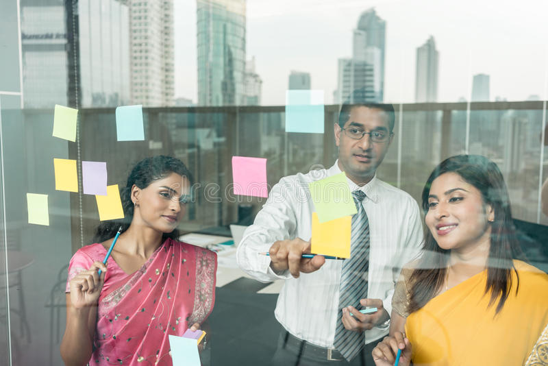 Indian employees sticking reminders on glass wall in the office. Three Indian employees sticking reminders on glass wall with business tasks and deadlines in the stock photography