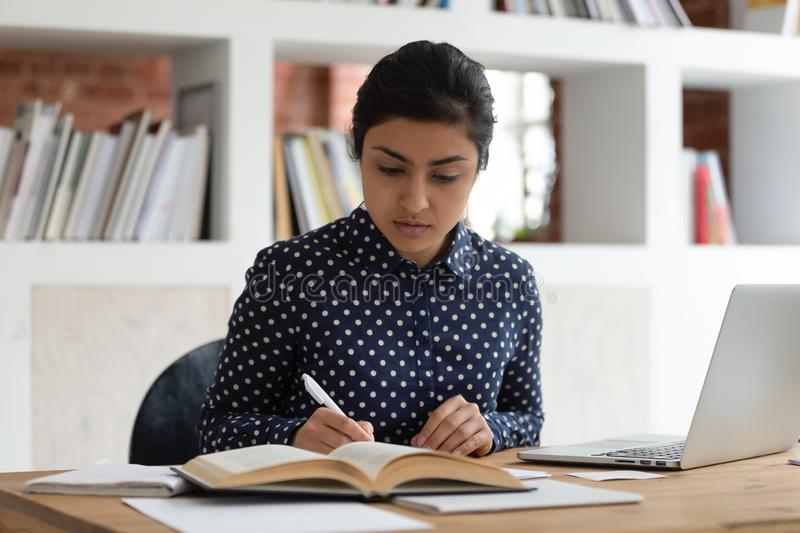 Indian ethnicity student woman writing notes reading textbook studying indoors. Indian student millennial woman writing notes reading textbook studying sitting royalty free stock images