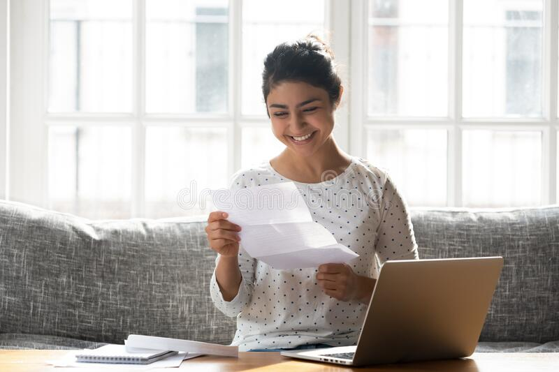 Happy woman holding paper reading good news college admission concept. Indian ethnicity woman sitting on couch at home reading paper notice receive good news stock images