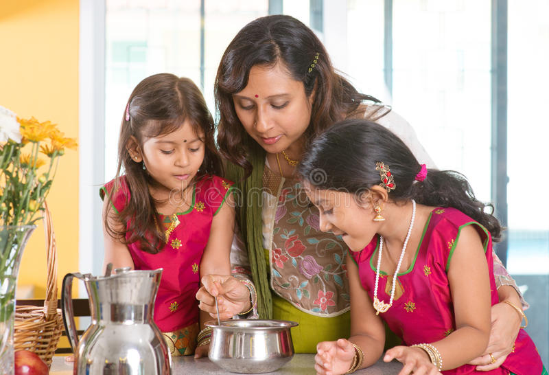 Indian family cooking. Asian family cooking food together at home. Indian mother and children preparing meal in kitchen. Traditional India people with sari
