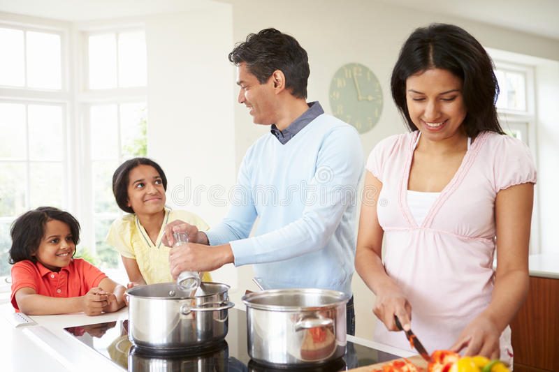 Indian Family Cooking Meal At Home. In Kitchen Talking To Each Other royalty free stock images